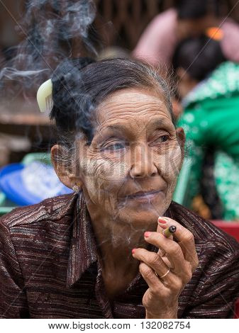 YANGON MYANMAR - JANUARY 10 2016: Unknown old woman sitting on the street smoking a cigarette. The people of Myanmar friendly to tourists