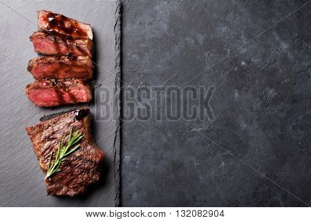 Grilled sliced beef steak with balsamico and rosemary on stone table. Top view with copy space