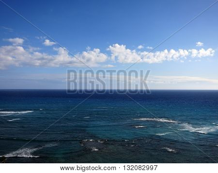 Shallow wavy ocean waters of Waikiki looking into the pacific ocean with blue sky and clouds on Oahu.