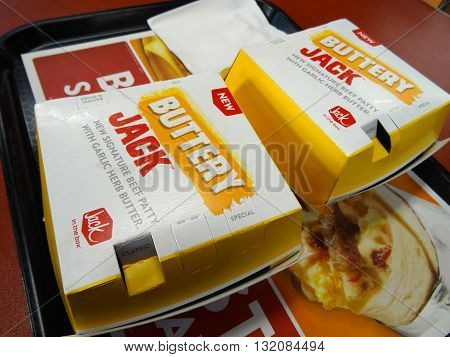 HONOLULU - SEPTEMBER 1: Two Buttery Jack Burgers in Boxs with white paper napkin on black plastic tray. The Buttery Jack is the new signature beef patty with garlic herb butter from Jack in the Box in Honolulu Hawaii on September 1 2015.