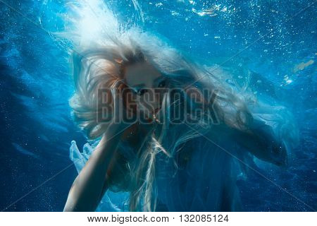 Woman with long blonde hair under the water it looks like a mermaid.