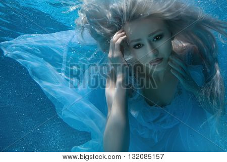 Blonde woman under water her long hair and a white dress.