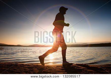Runner In Sun Rays On Beach. Sportsman In Baseball Cap, Jogging During The Sunrise Above Sea