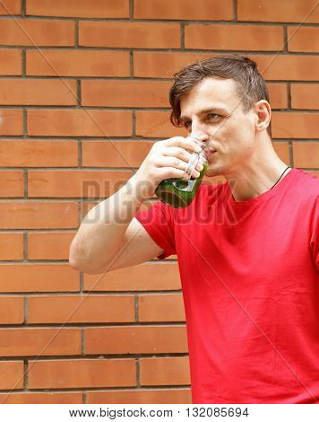 young man drinks healthy green smoothie in a glass jar