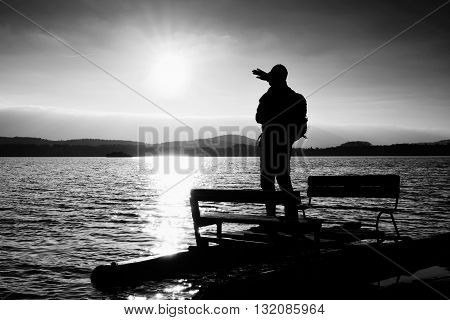 Hiker Silhouette With Backpack On Abandoned  Pedal Boat In The Sunset. Autumn Sun Above  Sea