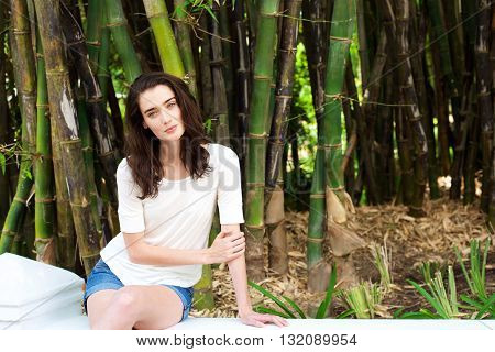 Beautiful Young Woman Sitting By Bamboo Trees