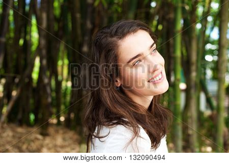 Attractive Young Woman Smiling In Front Of Bamboo Trees