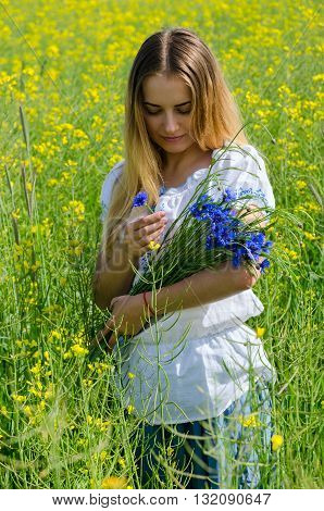 Beautiful girl with a bouquet of cornflowers on rapeseed field
