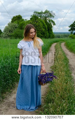 Beautiful young woman stands with basket of wild flowers on rural road among fields