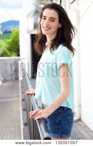Young Woman With Hands On Railing Smiling