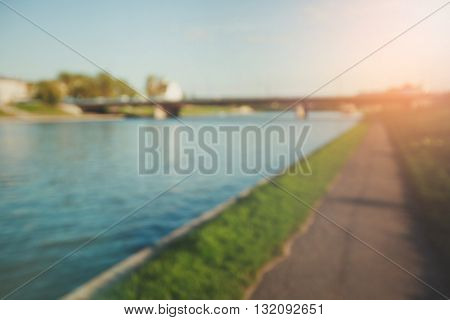 Blurred countryside background of river, bridge, green grass and road for walking or for bicycles.
