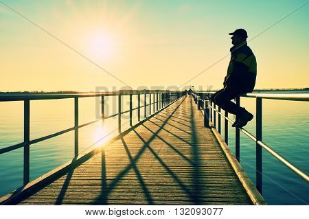 Man In Warm Jacket And Baseball Cap Sit On Pier Handrail Construction And Enjoy Morning At Sea.