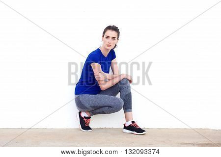 Young Sporty Woman Crouching Beside White Wall