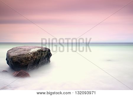 Romantic Atmosphere In Peaceful Morning At Sea. Big Boulders Sticking Out From Smooth Wavy Sea. Pink