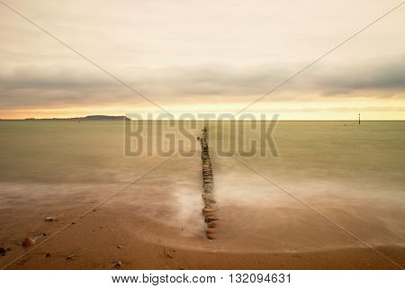 Wooden Breakwater On Wavy Baltic Sea.  Pink Horizon With First Hot Sun Rays.