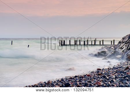 Abandoned wooden wharf in sea within sunrise.Gentle blue pink color of sky blur waves on water level.