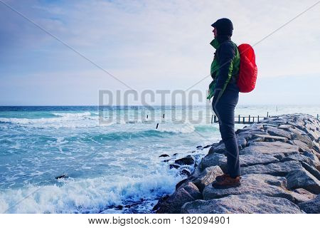 Tall Hiker In Dark Sportswear With Sporty Backpack On Beach,  Horizon With Blue Sky With Clouds.