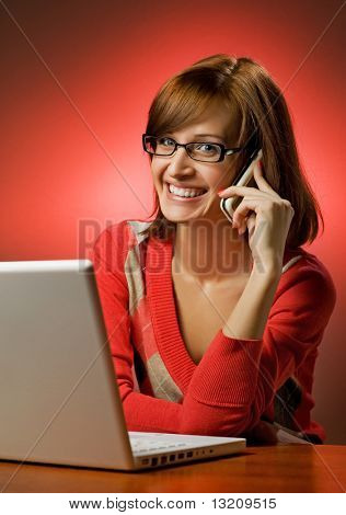 Beautiful smiling woman working on her laptop and talking on cell phone