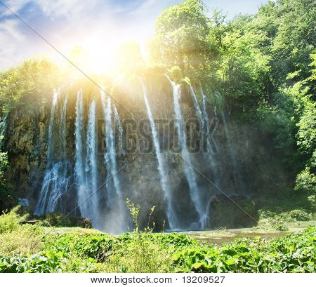 Sunrise over waterfall in wild forest