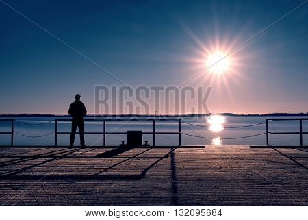 Man Stand On Wharf Construction And Looking At Sea. Sunny Clear Blue Sky, Calm Level
