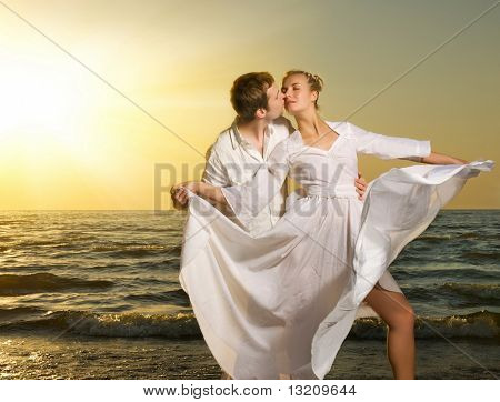 Young couple in love on a beach at sunset