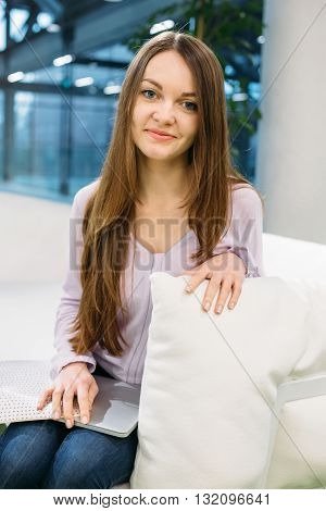 Open emotional girl business style works with a laptop on the couch in the business centers training and self-improvement technology positive attitude