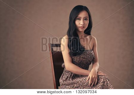 Unsmiling Vietnamese girl sitting on chair and looking at camera