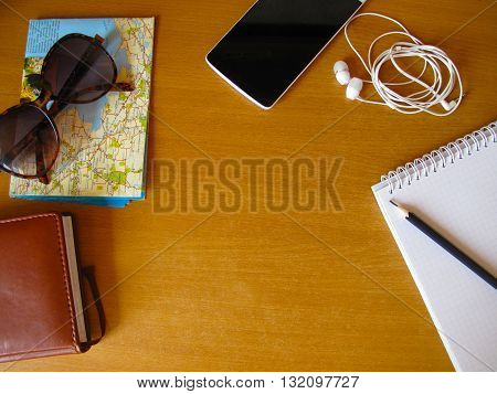 travel concept flay lay, sunglasses, map, headphones, phone, pencil, copybook