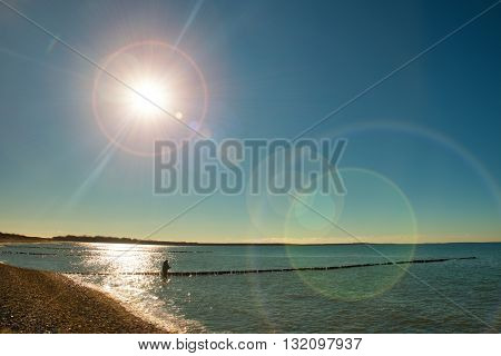 Fisher With Rod In Golden Sunshine With Beautiful Sea. Fishing At Breakwaters In Sea