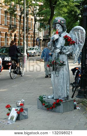 AMSTERDAM, HOLLAND - SEPTEMBER 03, 2005: Human statue dressed as angel on the street