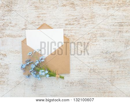 Brown paper envelope with white blank card and blue forget-me-not flowers bouquet tied with jute rope on the rustic white painted background