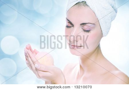 Beautiful young woman with aroma bath ball over abstract blurred background