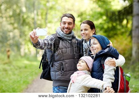 travel, tourism, hike, technology and people concept - happy family with backpacks taking selfie by smartphone in woods
