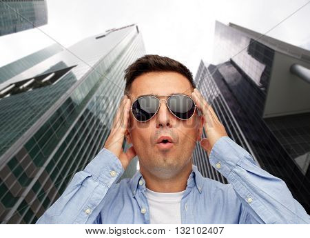 summer, emotions, style and people concept - face of scared or surprised middle aged latin man in shirt and sunglasses over city skyscrapers background