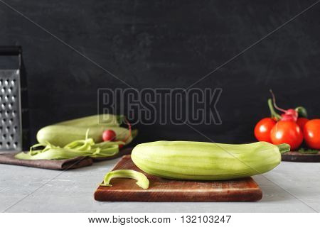 Marrow on a wooden cutting board closeup on a light table on a dark background with space for your text. Cooking useful food