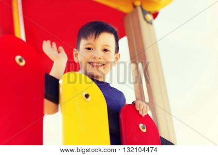 summer, childhood, leisure, gesture and people concept - happy little boy waving hand on children playground climbing frame
