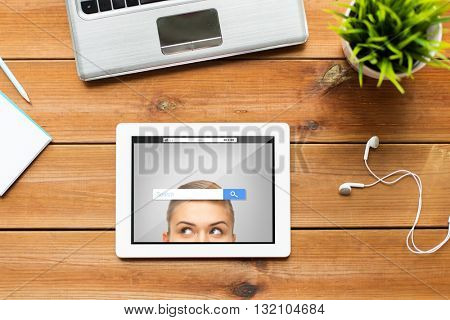 education, business and technology concept - close up of tablet pc computer, laptop and earphones on wooden table with internet search bar on screen