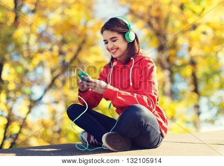 technology, season and people concept - smiling young woman or teenage girl with smartphone and headphones listening to music over autumn park background