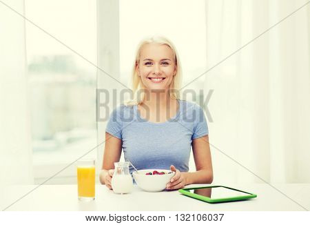 healthy eating, dieting and people concept - smiling young woman with tablet pc computer eating breakfast at home