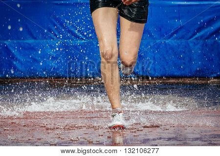 athlete foot women running steeplechase. a spray of water