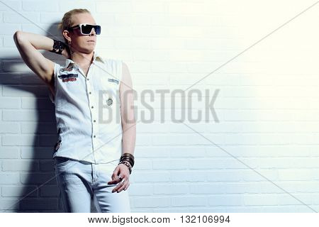 Modern young man in jeans clothes posing by the white brick wall. Youth fashion.