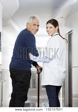 Rear View Of Happy Doctor Walking With Senior Patient