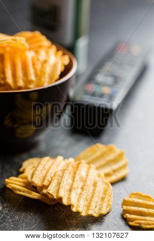 Crinkle cut potato chips on table. Tasty spicy potato chips and tv remote controller.