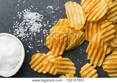 Crinkle cut potato chips on kitchen table. Tasty spicy potato chips with salt.Top view.