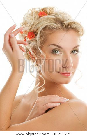 Beautiful young woman with fresh spring flowers in her hair close-up portrait