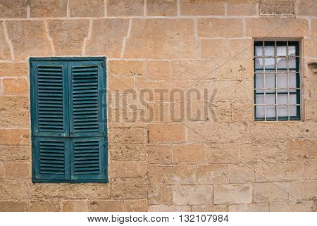 Two windows on the stone wall of an old house in the former capital of island Malta - Mdina. Closed green shutter the other window without shutter.
