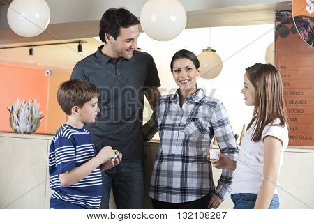Smiling Woman Standing With Family In Ice Cream Parlor