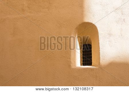 Facade of an old house with an old window with an arch in arabian style. Wall partly enlightened by the sunlight. Former capital of Malta - Mdina.