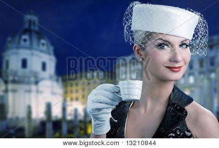 Bella joven tomando café. Antiguo fondo de ciudad detrás de ella