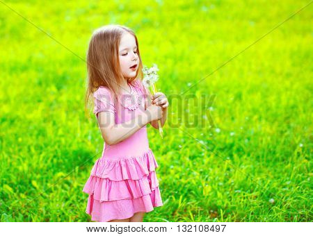 Little Girl Child Blowing Dandelions Flowers In Spring Sunny Field